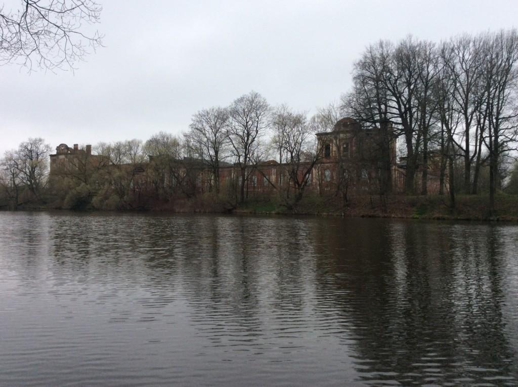 На противоположном берегу Верхнего пруда сквозь деревья видны остатки великолпеного Конюшенного корпуса