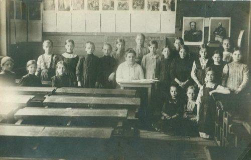 Ученики сельской школы.На стене справа висят портреты императора Александра Первого и Михаила Кутузова. Начало 20 века
